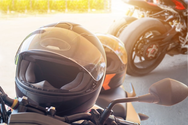 Homem em uma motocicleta com capacete e luvas é um importante vestuário de proteção para controle de aceleração de motociclismo com luz do sol.