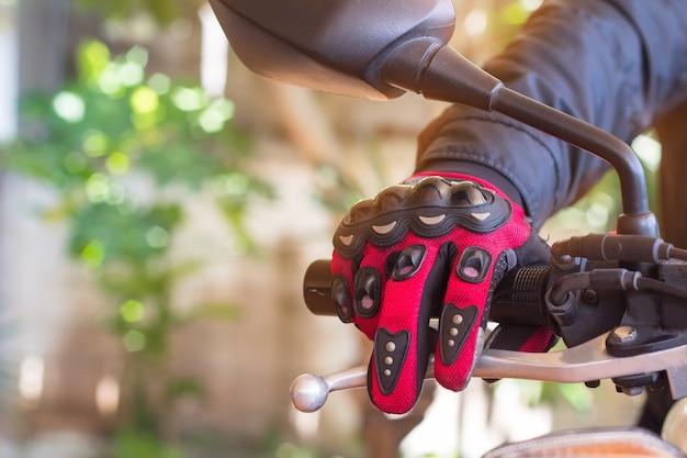 Homem em uma motocicleta com luvas é roupas de proteção para o motociclismo