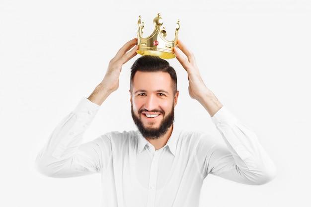 Homem em uma parede branca usa uma coroa na cabeça,