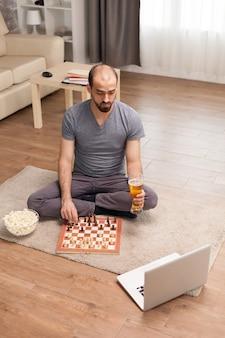 Homem em uma videochamada jogando xadrez com amigos e segurando um copo de cerveja durante o auto-isolamento.