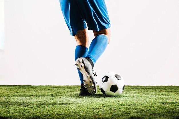 Homem, em, uniforme azul, chutando bola