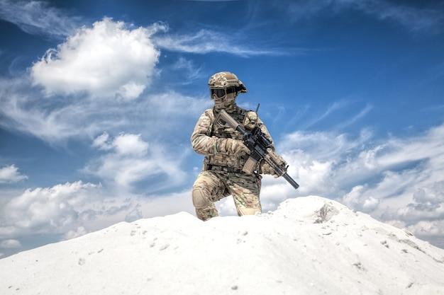 Homem em uniforme de camuflagem militar com réplica de rifle de serviço, em pé no topo de uma duna de areia com céu nublado no fundo, imitando o atirador das forças especiais do exército dos eua durante jogos de guerra de airsoft no deserto