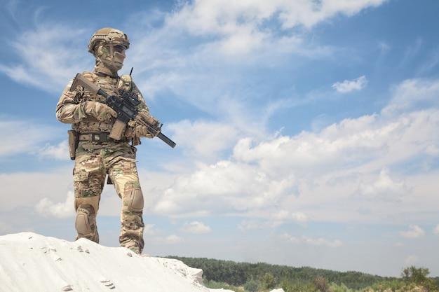 Homem em uniforme de camuflagem militar e máscara, munição tática equipada, em pé na duna de areia com réplica de rifle de serviço nas mãos, céu nublado no fundo. jogador de airsoft participando de jogos de guerra