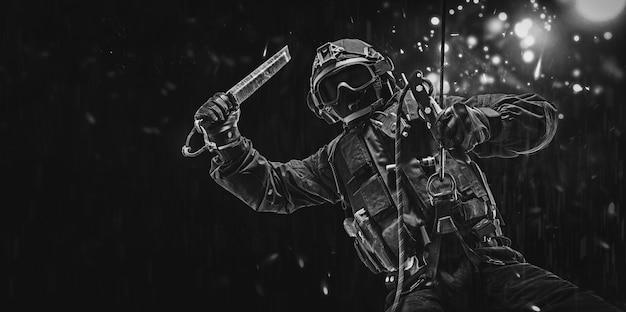 Homem em uniforme militar está pendurado em uma corda e balança um dispositivo especial para quebrar janelas