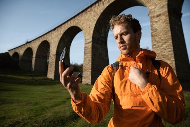Homem em viagem segurando uma bússola em frente ao aqueduto