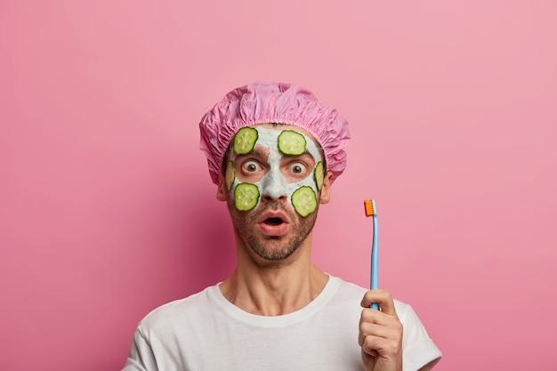 Homem emocionado e atordoado com medo, segura a escova de dentes, usa touca de banho e camiseta casual, quer ter dentes saudáveis