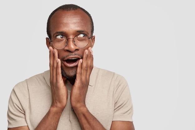 Homem emocionado e surpreso tocando as bochechas e olhando com admiração à parte