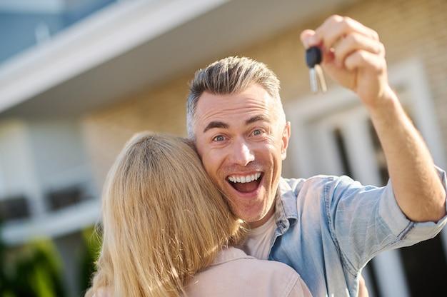 Homem emocional brilhante com a chave e a esposa de volta