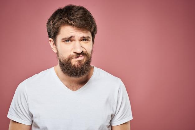 Homem emocional, camiseta branca, expressão facial triste isolada