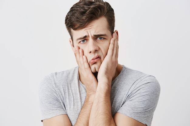 Homem emocional chocado chocado mantém as mãos nas bochechas, sendo incomodado em ouvir conselhos de seus pais isolados contra o fundo da parede em branco do estúdio. homem europeu não pode acreditar em notícias chocantes