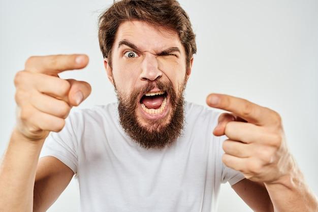 Homem emocional com barba gesticulando com sua agressão de estúdio de mãos.