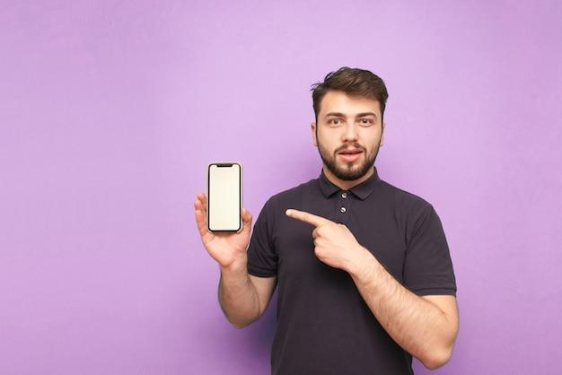Homem emocional com barba, vestindo uma camiseta escura e segurando um smartphone com uma tela branca na mão