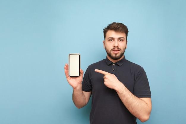 Homem emocional com barba, vestindo uma camiseta escura segura um smartphone com uma tela branca na mão, mostra um dedo