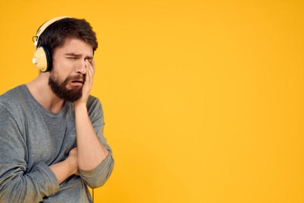 Homem emocional com fones de ouvido, ouvindo música, tecnologia de fundo amarelo