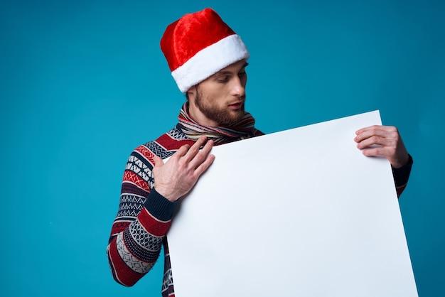 Homem emocional com um chapéu de papai noel segurando um banner de férias em estúdio posando