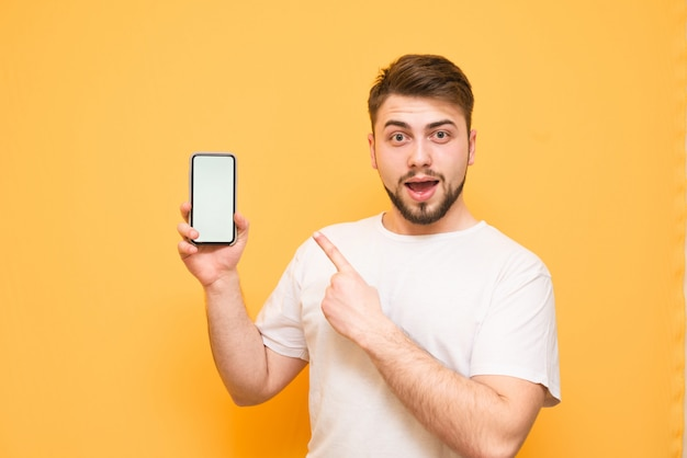 Homem emocional com uma barba, vestindo uma camiseta branca segura um smartphone com uma tela branca na mão, mostra um dedo, olha na câmera em um amarelo