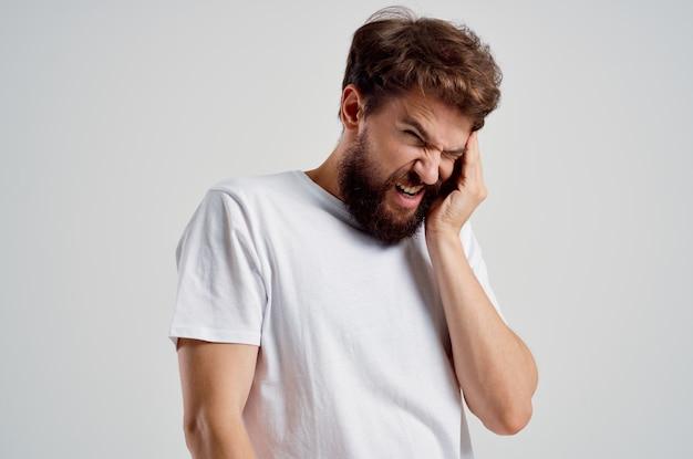Homem emocional com uma camiseta branca, dor de cabeça, enxaqueca, problemas de fundo claro