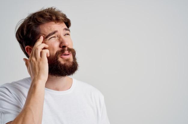 Homem emocional com uma camiseta branca, dor de cabeça, enxaqueca, tratamento em estúdio