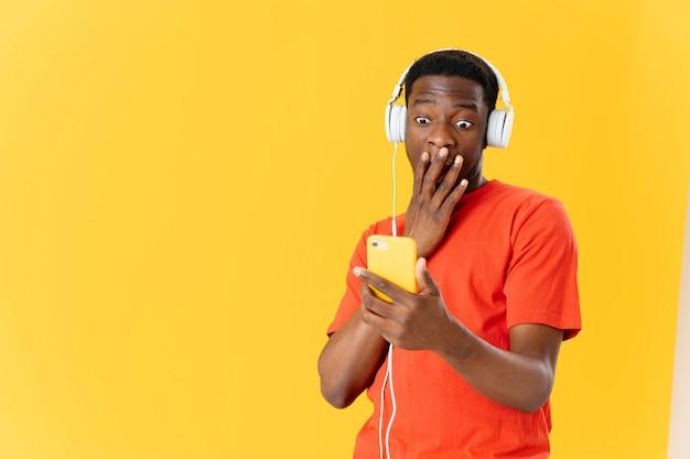 Homem emocional de aparência africana em fones de ouvido, ouvindo música de fundo isolado