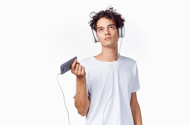 Homem emocional de camiseta branca ouvindo música com fones de ouvido