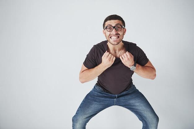 Homem emocional em roupas casuais e com óculos se segura pelo colarinho de uma camiseta