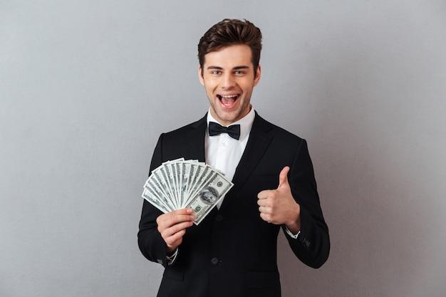 Homem emocional em traje oficial segurando dinheiro aparecendo polegares.