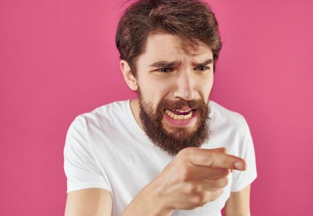 Homem emocional em uma camiseta branca com visual expressivo e fundo rosa
