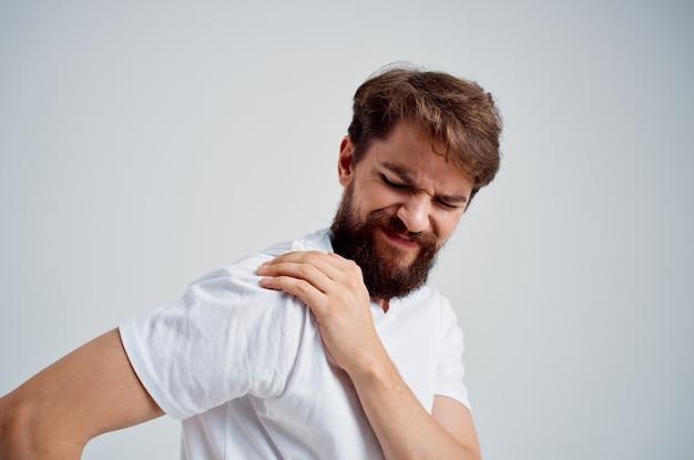 Homem emocional em uma camiseta branca estresse remédio para dor no pescoço isolado fundo