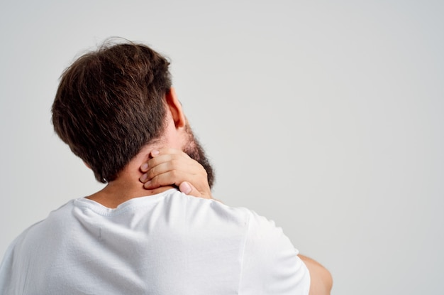 Homem emocional em uma t-shirt branca estresse remédio dor no pescoço luz de fundo. foto de alta qualidade