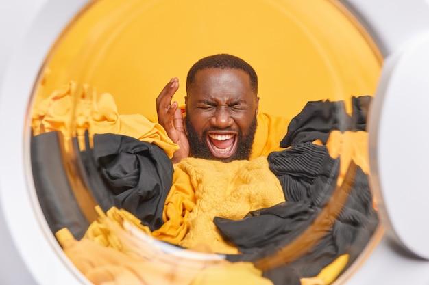 Homem emocional levanta a mão, carrega roupas na máquina de lavar, exclama em voz alta