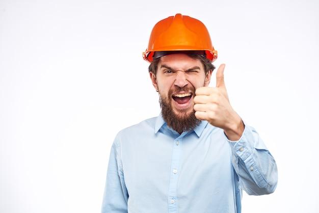 Homem emocional na camisa azul laranja capacete indústria segurança profissional.