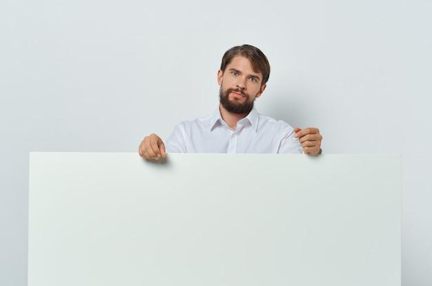 Homem emocional na camisa gesticulando com o anúncio de negócios de maquete brancas de mãos. foto de alta qualidade