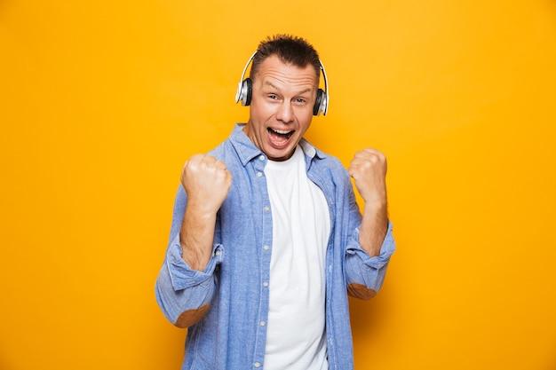 Homem emocional ouvindo música com fones de ouvido faz gesto de vencedor.