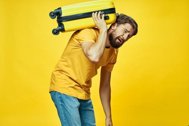 Homem emocional segura nas costas um passageiro de mala pesada