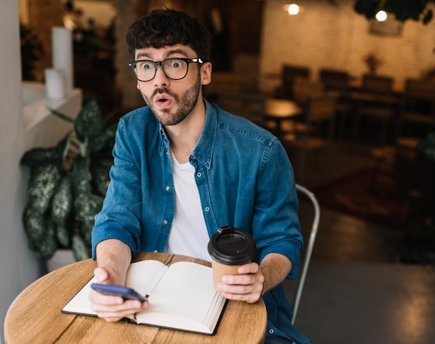 Homem emocional, segurando a xícara de café e smartphone no café