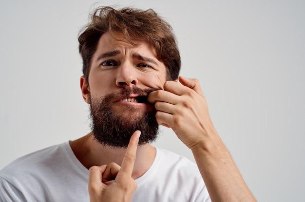 Homem emocional segurando para enfrentar a dor em um fundo isolado de dentes