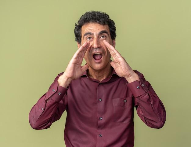 Homem emocional sênior com camisa roxa gritando com as mãos perto da boca em pé sobre o verde
