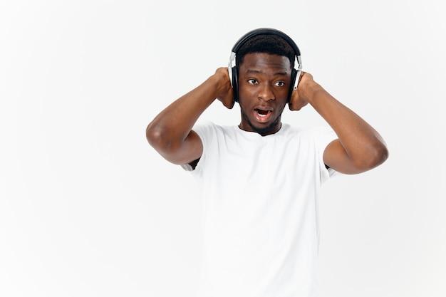 Homem emocionalmente africano com fones de ouvido, amante da música, tecnologia