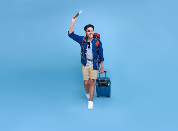 Homem empacotador de bolsa asiática sorridente feliz com passaporte e bagagem, desfrutando de sua escapadela de férias de verão em fundo azul.