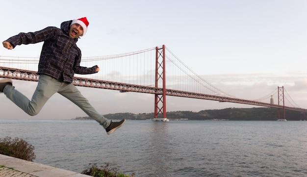 Homem empolgado a pular no ar com o chapéu vermelho de natal à beira do rio tejo e a ponte 25 de abril atrás