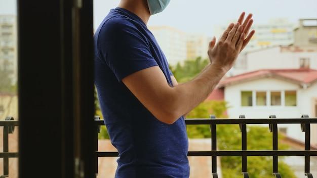Homem empolgado com máscara de proteção na varanda do apartamento batendo palmas para médicos na luta contra covid-19.