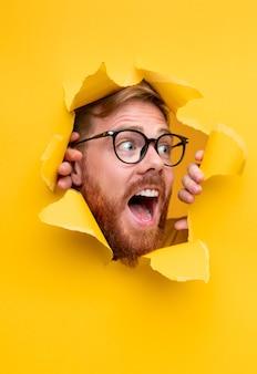 Homem empolgado de óculos olhando pelo buraco do papel rasgado