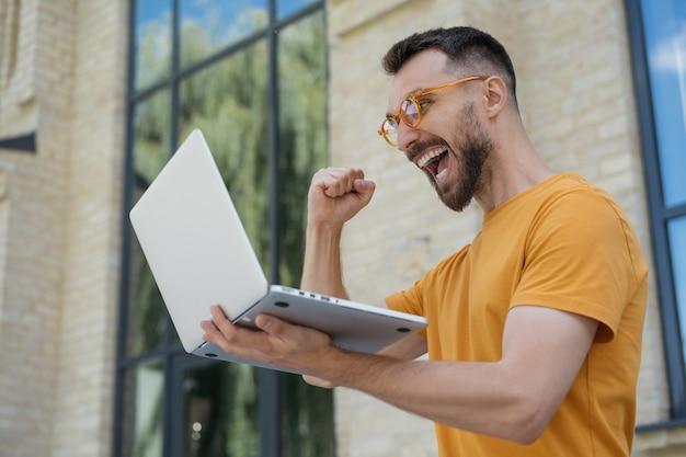 Homem empolgado usando laptop jogando videogame, apostas esportivas