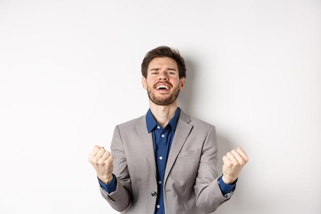 Homem empolgado vencendo no cazino e comemorando, fazendo o punho bombear e gritando sim com uma expressão feliz, atingir o objetivo, triunfar, pisando em um fundo branco.