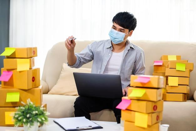 Homem empreendedor trabalhando com laptop e verificando a preparação da caixa de pacotes para entrega ao cliente no escritório doméstico, ele usa uma máscara facial para proteger a pandemia de coronavírus