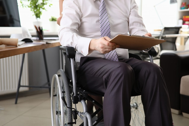 Homem empregado trabalhando em um escritório na cadeira de rodas