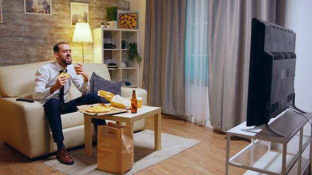 Homem empresário com gravata comendo pizza e rindo assistindo tv depois do trabalho, sentado no sofá.