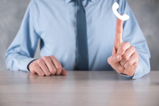 Homem empresário com uma camisa e uma gravata na superfície cinza segura o ícone do telefone