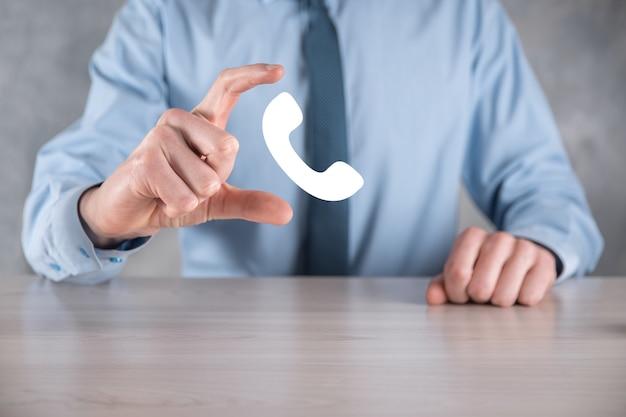 Homem empresário com uma camisa e uma gravata no fundo cinza segura o ícone do telefone
