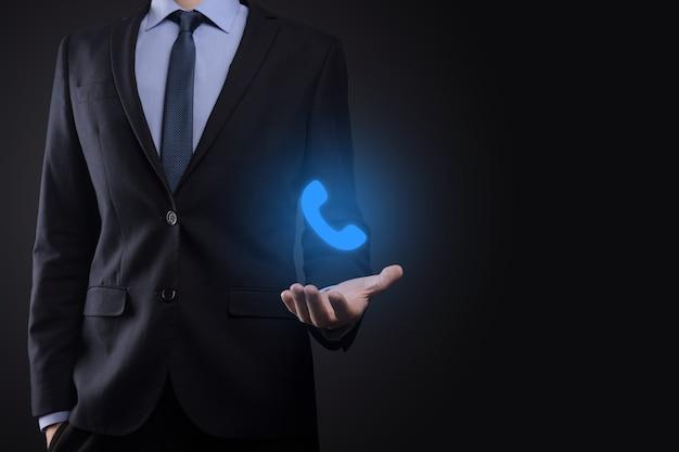 Homem empresário de terno em fundo preto segurando o ícone do telefone